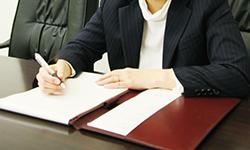 机に座る男性とノートとペン